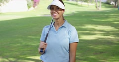 Young woman golfer strolling across the course - stock footage
