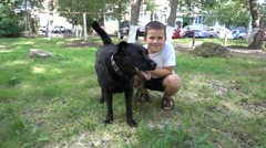 Boy and his dog play on the grass Stock Footage