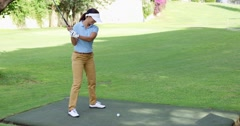 Young female golfer preparing to tee off Stock Footage