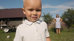 Cute Little Boy Standing In Front of Camera In The Garden In Summer. Mom On Stock Footage