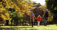 Mother dad and daughter walking hand in hand outdoors Stock Footage