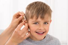 Close-up Of A Doctor Fitting Hearing Aid On Smiling Boy's Ear Stock Photos