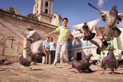 Grandparents And Grandson Boy Chasing Pigeons Flying Stock Photos