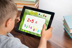 Close-up Of Boy Solving Math Problem On Digital Tablet In Classroom Stock Photos