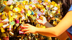 Young woman touching padlocks attaches on a bridge fence as a symbol of love Stock Footage