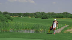 Woman carries a golf bag - stock footage