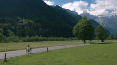 Aerial - Distant shot of a woman in a white dress riding bicycle on rural road Stock Footage