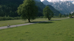 Aerial - Woman in a short white dress riding bicycle on rural road Stock Footage