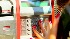Young woman uses the public telephone on the street close up Stock Footage