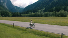 Aerial - Tracking shot of a woman in a white dress riding bicycle on rural road Stock Footage
