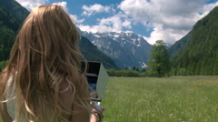 Young woman standing in the meadow and holding remote control to fly drone Stock Footage