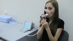 Girl breathes into a spirometer tube closed-toe to check the oxygen in the lungs Stock Footage
