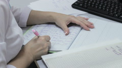 Doctor writes a medical journal for notes Stock Footage