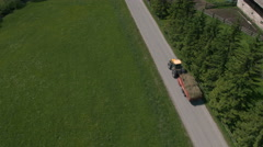 Aerial - Tractor driving through the valley with a trailer full of dried hay Stock Footage