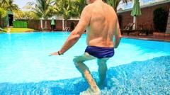 European Bearded Old Man Walks into Swimming Pool Stock Footage