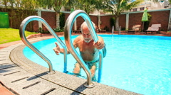 Bearded Old Man Comes out of City Pool by Ladder Closeup Stock Footage