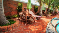 Bearded Old Man Stands up of Chair Dives into Pool Stock Footage