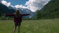 Happy woman standing in the meadow and raising arms Stock Footage