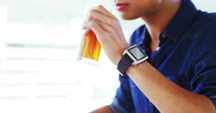 Man sipping drink wearing smartwatch Stock Footage