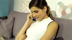 Beautiful woman making phone call to boyfriend sitting on sofa 4K - stock footage