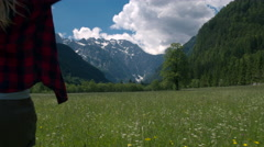 Back view of a woman standing in the meadow and raising arms Stock Footage