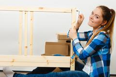 Woman assembling wooden furniture. DIY. Stock Photos