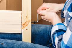 Assembling wood furniture using hex key. DIY. - stock photo