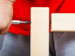 Assembling wood furniture using scredriver. DIY. - stock photo