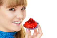 Woman holds cupcake trying to resist temptation - stock photo