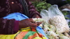 Side view of a peruvian woman picking apart giant corn Stock Footage