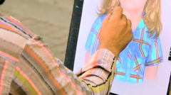 Street painter draws a portrait of girl on the paper with pencil Stock Footage