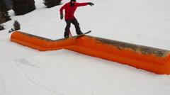 Snowboarder sliding on tube steadicam shot Stock Footage