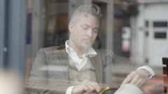 4K Pensive man sitting alone in cafe, looking out of window & using computer tab Stock Footage