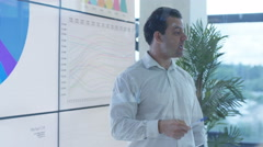 4K Businessman giving presentation to colleagues in modern glass office Stock Footage