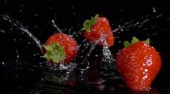 strawberries rain splashing on water slow motion - stock footage