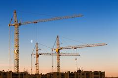construction cranes, building against blue sky with Moon at dawn - stock photo