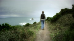 Young man hiking trail on Pacific Ocean, Cape Blanco state park, OR Stock Footage