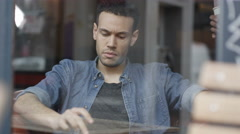 4K Cheerful young man sitting alone in cafe using computer tablet - stock footage