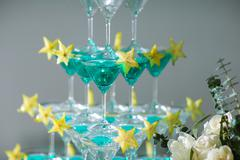 the pyramid of glasses with champagne and a carambola - stock photo