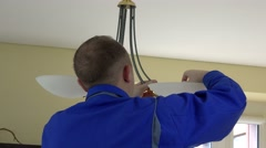 Electrician guy changing light bulbs in chandelier. Back view Stock Footage