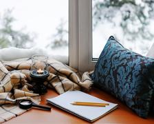 Open notepad, magnifier glass, pillow, candle, pencils and plaid. - stock photo