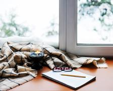 Open notepad, glasses, candle, pencil and beige warm plaid. Stock Photos