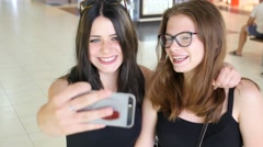 Two cute teen age girls smile have fun shooting selfie photo in public place Stock Footage