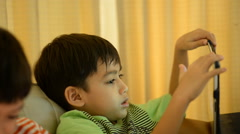 Little sibling boy playing game tablet mobile together Stock Footage