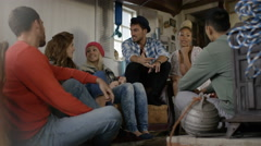 4K Happy group of friends hanging out & chatting in cabin on the beach Stock Footage