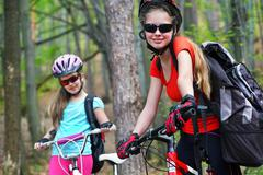 Bikes girls. Happy family wearing helmet are cycling on bicycles . Stock Photos