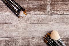 Cosmetic brushes on wooden background - stock photo