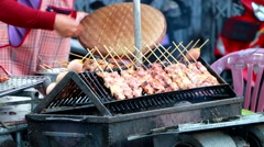 Local Cook local Thai styled pork babeque at famous Kad Kong Ta walking street Stock Footage