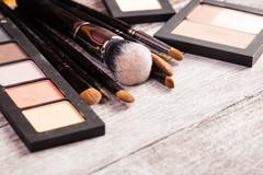 Make up brushes with cosmetics products next to them Stock Photos