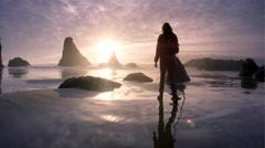 Woman hiking beach at sunset, Oregon Coast, Bandon, OR Stock Footage